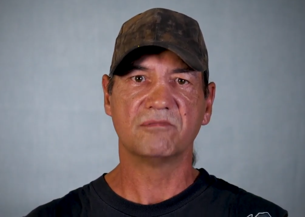 An indigenous man in a brown hat and black shirt.